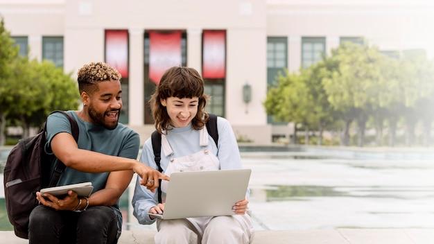 Alunos estudando em um laptop no campus da faculdade