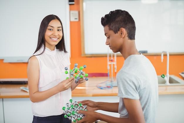 Alunos experimentando modelo de molécula em laboratório