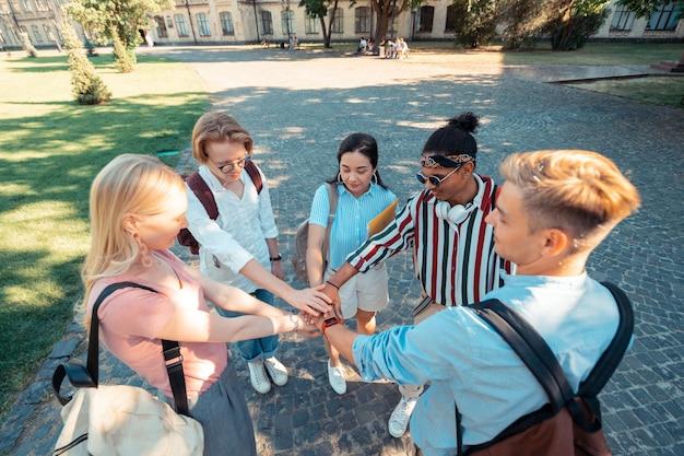 Alunos felizes de mãos dadas formando um círculo