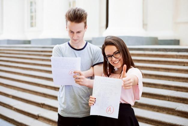 Alunos felizes e tristes com resultado do teste perto de escadas da antiga instituição convencional