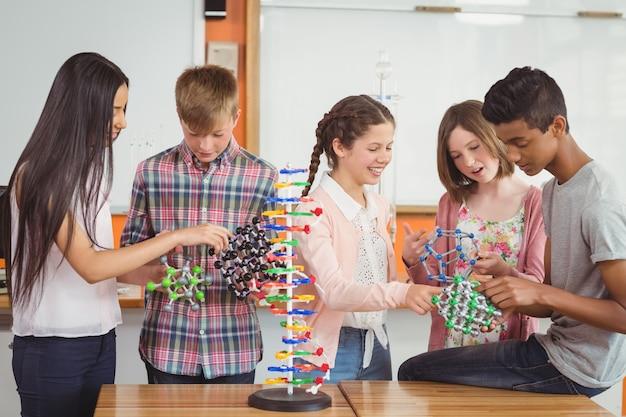Alunos felizes experimentando modelo de molécula em laboratório