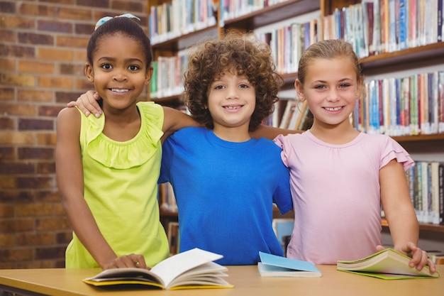 Alunos felizes lendo um livro da biblioteca