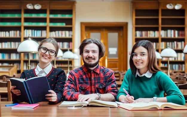 Alunos felizes na biblioteca, sorrindo para a câmera