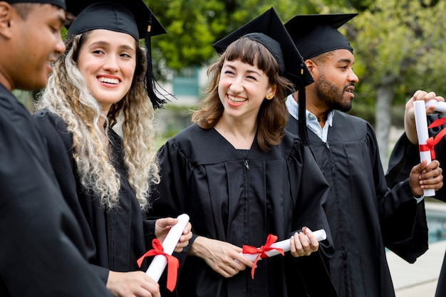 Alunos felizes se formando na universidade, comemorando com diplomas