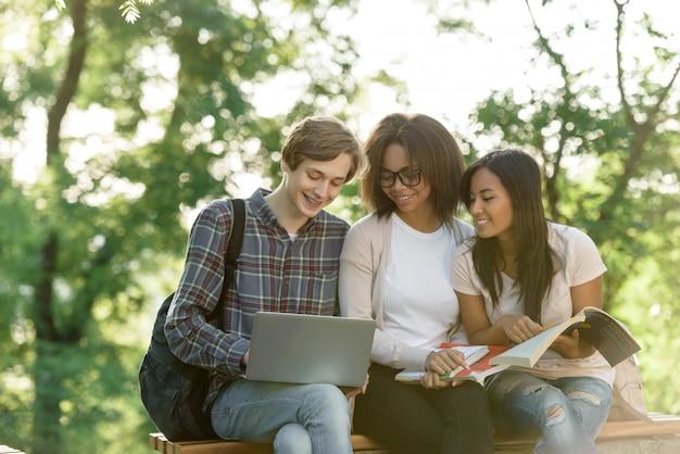 Alunos felizes sentado e estudando ao ar livre enquanto estiver usando o laptop