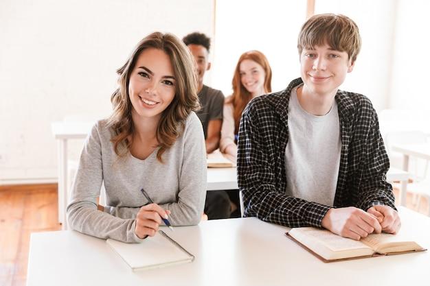 Alunos felizes sentados na sala de aula dentro de casa olhando a câmera.