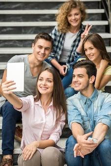 Alunos felizes sentados nas escadas e tomando selfie.