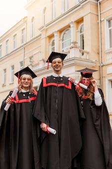 Alunos graduados felizes de baixo ângulo
