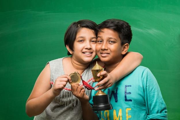 Alunos indianos asiáticos segurando uma taça de troféu de ouro sobre o fundo verde do quadro-negro