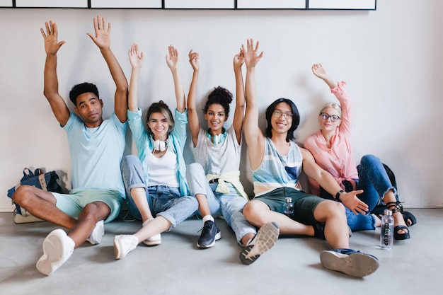 Alunos inspirados felizes posando com as mãos ao alto porque os exames acabaram. retrato interno de felizes colegas de universidade se divertindo no campus antes das férias.
