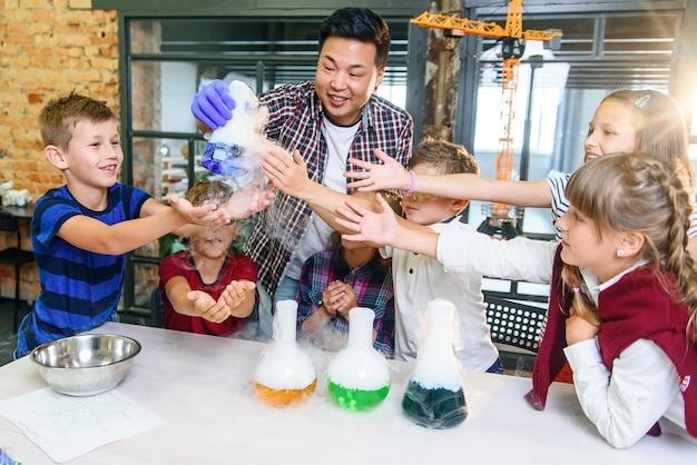Alunos interessados estudam as reações químicas da troca no exemplo de líquidos coloridos em frascos de vidro.