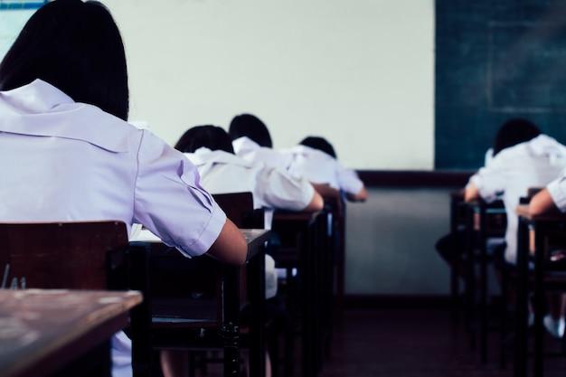 Alunos lendo e escrevendo respondem a fazer o exame em sala de aula.