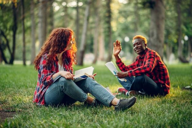 Alunos lendo livro na grama no parque de verão. adolescentes masculinos e femininos estudando ao ar livre e almoçando