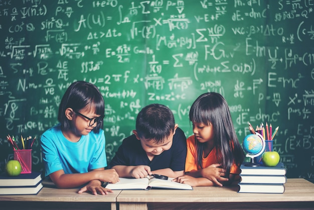 Alunos lendo um livro na sala de aula.