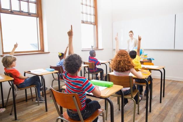 Alunos levantando as mãos durante a aula