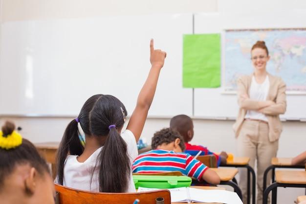 Alunos levantando mão durante a aula de geografia na sala de aula