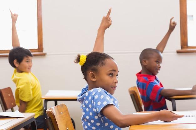 Alunos levantando mão na sala de aula