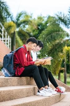 Alunos masculinos e femininos, sentado e lendo livros nas escadas.