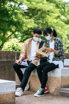 Alunos masculinos e femininos usando máscaras sentam e leem livros nas escadas