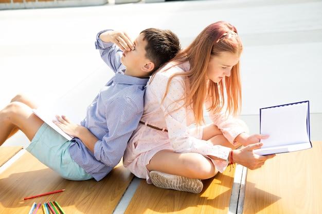 Alunos menina e menino adolescentes de 11 anos estudam no pátio da escola, sentam no banco, o menino está cansado, a menina está lendo um livro