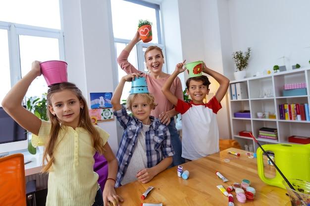 Alunos mostrando baldes. alunos da escola primária mostrando seus baldes coloridos para plantas após a aula de ecologia