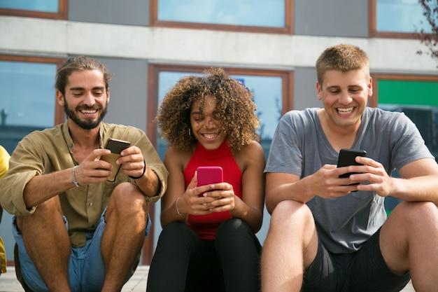 Alunos multiétnicos focados alegres usando seus telefones