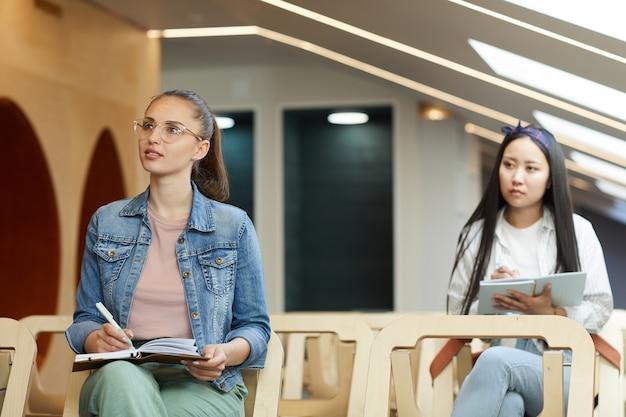 Alunos multiétnicos pensativos em trajes casuais sentados com a apostila na sala de aula e ouvindo o professor