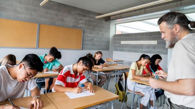 Alunos multirraciais do ensino médio fazendo um teste professor de olho neles copiar banner espaço