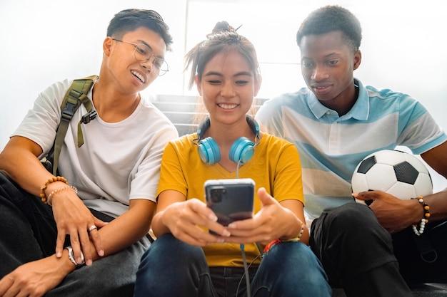 Alunos multirraciais do ensino médio olhando para o celular de uma garota de volta às aulas vício em tecnologia