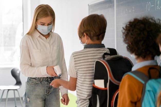Alunos na escola alinhados para verificação de temperatura por professora