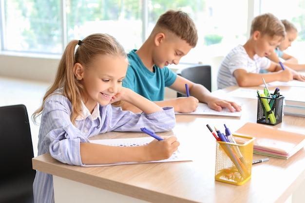 Alunos passando no teste escolar em sala de aula