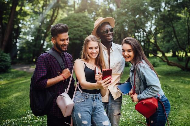 Alunos passando um tempo juntos no parque perto do campus usando o telefone celular