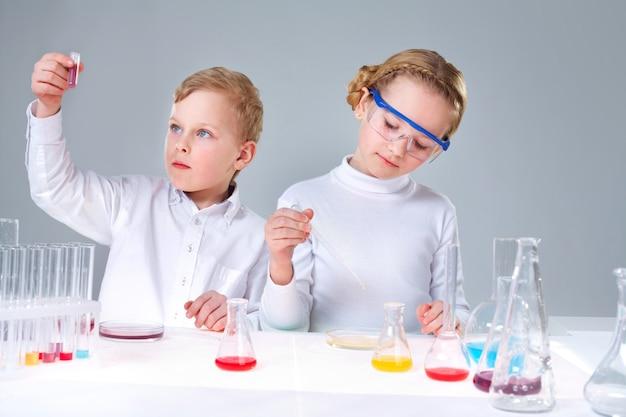 Alunos que analisam tubos de ensaio com líquidos