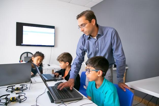 Alunos realizando tarefas em laptops e um professor focado monitorando-os
