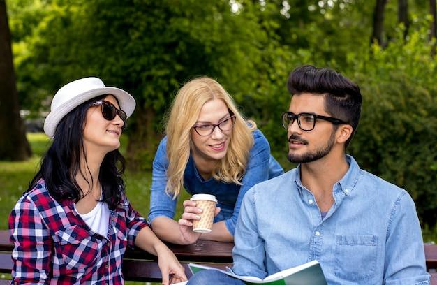 Alunos se divertindo enquanto fazem a lição de casa juntos no parque do campus