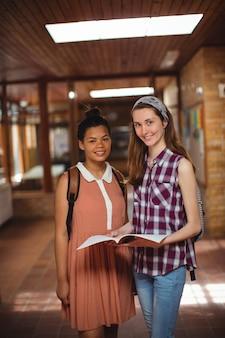 Alunos segurando livros no corredor da escola