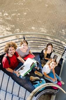 Alunos sentados com livros nas escadas