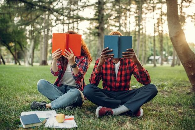 Alunos sentados na grama e cobrindo o rosto com livros, parque de verão