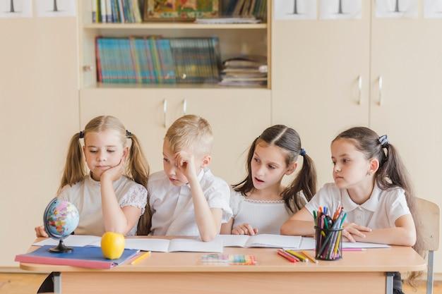 Alunos sentados na mesa da escola