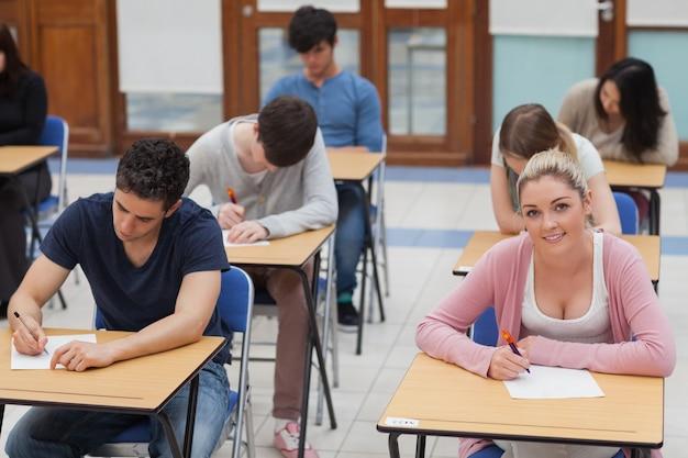 Alunos sentados na sala de exame, concentrando-se
