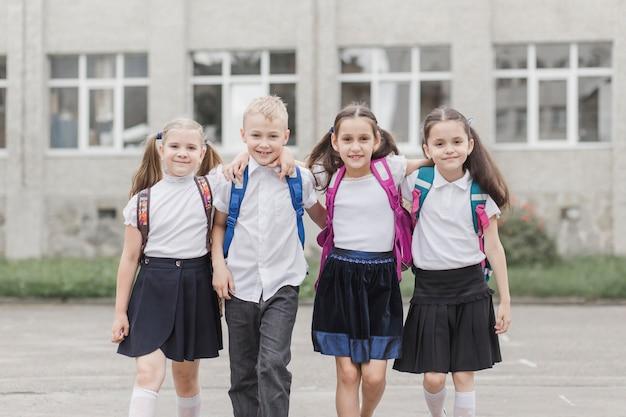 Alunos sorridentes abraçando perto da escola