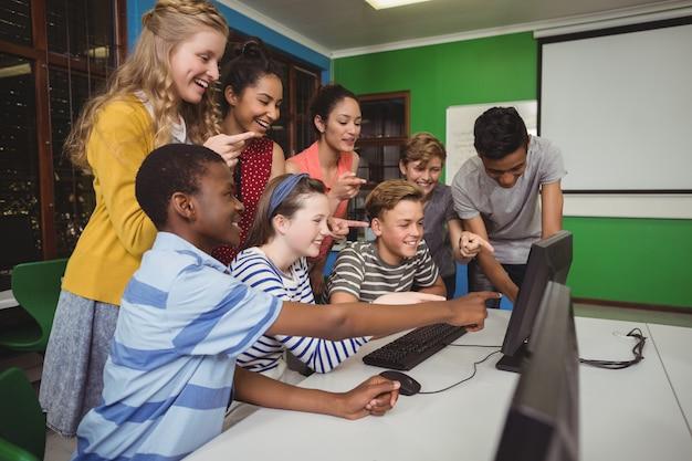 Alunos sorridentes estudando juntos na sala de informática