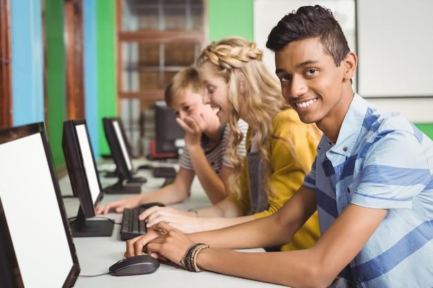 Alunos sorridentes estudando na sala de informática