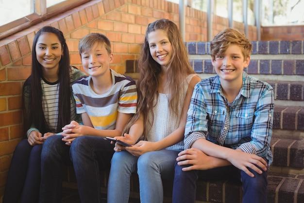 Alunos sorridentes sentados na escada usando um telefone celular