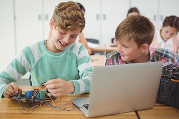 Alunos sorridentes trabalhando em projeto eletrônico em sala de aula