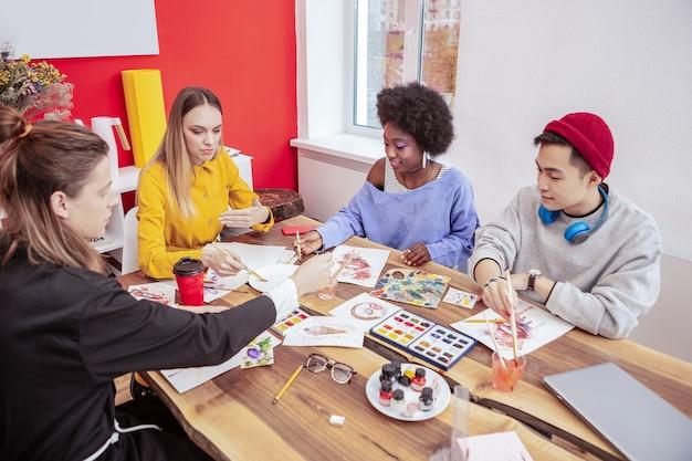 Alunos talentosos. estudantes talentosos e criativos de arte da moda se sentindo felizes trabalhando juntos