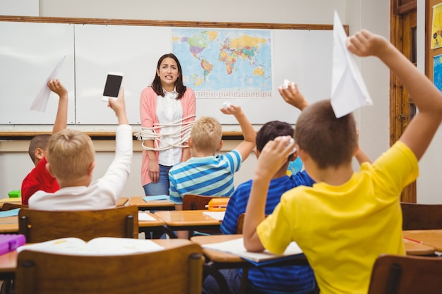 Alunos torcendo papel e aviões em sala de aula