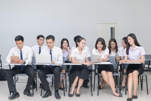 Alunos trabalhando com laptop em sala de aula
