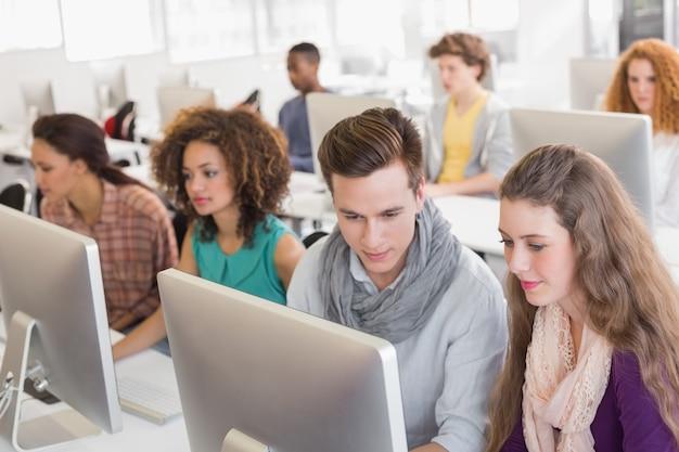 Alunos trabalhando na sala de informática da faculdade