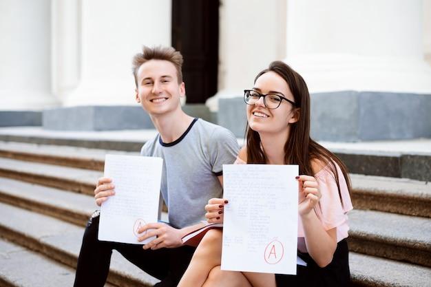 Alunos universitários alegres sentados ao ar livre nas escadas do edifício e apresentando excelentes resultados de teste